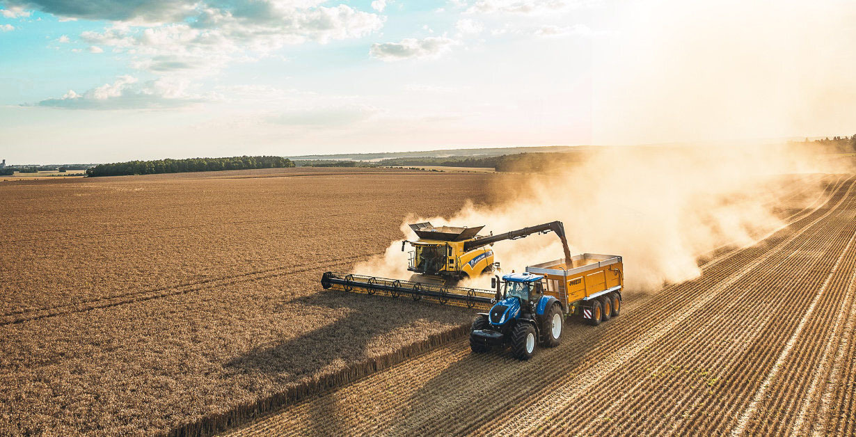 New Holland Combine taking up wheat and unloading. Novlan Agriculture